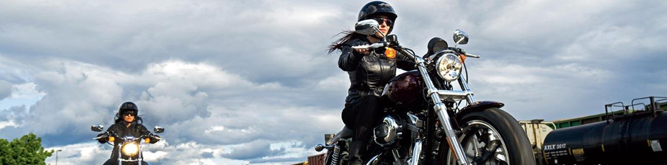 Two women ride motorcycles with a cloudy sky background.